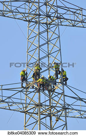 Stock Photograph of Overhead linemen working on a pylon.