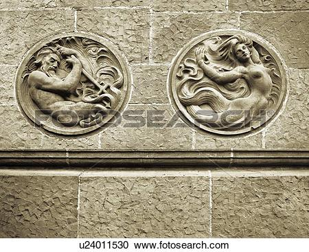 Stock Photography of Stone wall with carved out mermaid and.