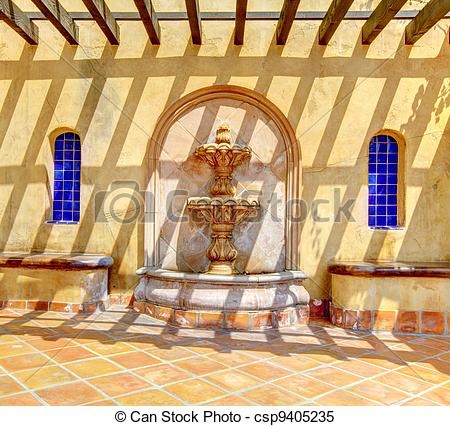 Stock Images of Spanish fountain detals with yellow wall.