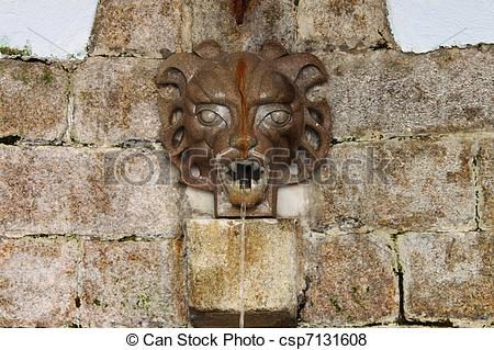 Pictures of Medieval wall fountain with gargoyle spitting water.