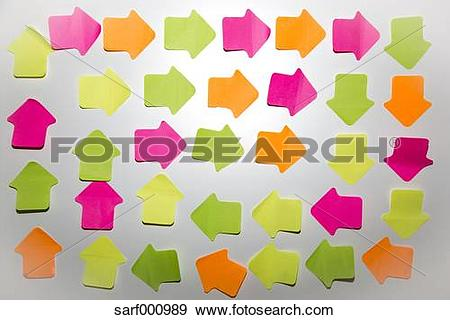 Stock Photograph of Coloured arrow shaped adhesive notes on white.