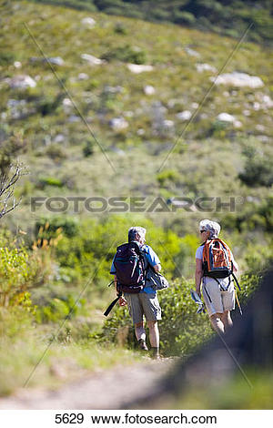 Stock Photograph of Mature couple hiking on mountain trail.