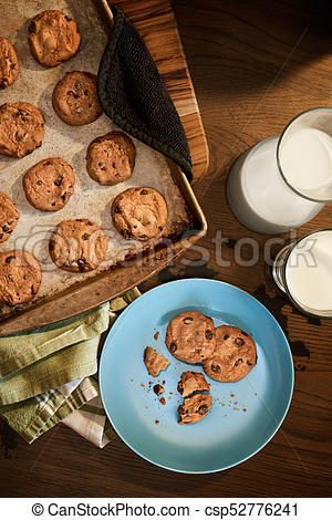 Overhead view of cookie sheet and plate of chocolate chip cookies warm from  the oven with glass of cold milk on vintage wood table.