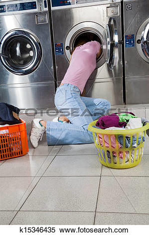 Stock Image of Woman Searching Clothes In Washing Machine Drum.