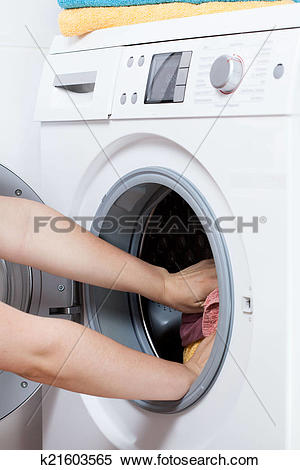 Stock Image of Hands putting laundry into the washing machine drum.