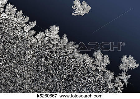 Picture of winter background frozen water crystals on gradual dark.