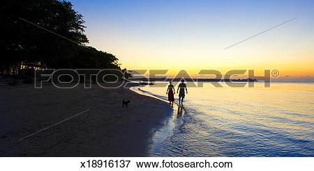 Picture of Couple Waking At Water Edge With Tropical Sunset.