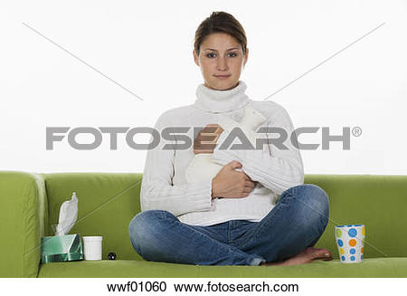 Stock Photography of Young woman sitting on sofa, holding hot.