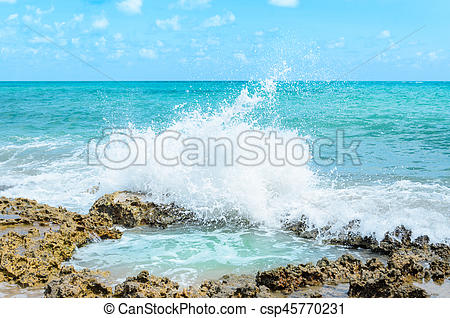 Ocean water splashing on rocks and forming a natural pool in the center of  the image. Sunny day, very beautiful, with water hitting rocks and throwing.