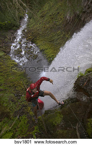 Stock Photography of A man rappelling with a kayak down a.