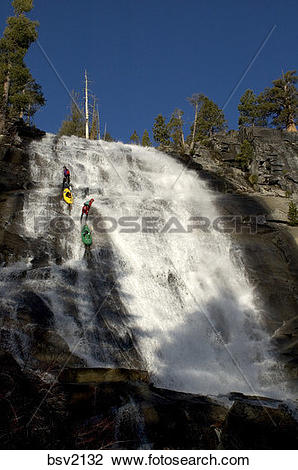 Stock Photo of Two men rappelling down a waterfall while kayaking.