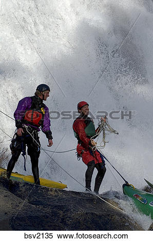 Stock Image of Two men coiling ropes after rappelling down a.