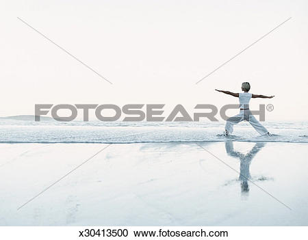 Stock Photography of Woman Stands on the Beach at the Water's Edge.