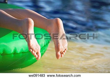 Stock Photo of Young girl lying on green float with toes pointed.
