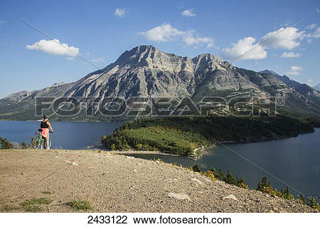 Stock Photo of A woman on her bicycle overlooking Waterton Lake.