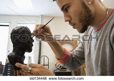 Pictures of Mixed race student carving wax figure in class.