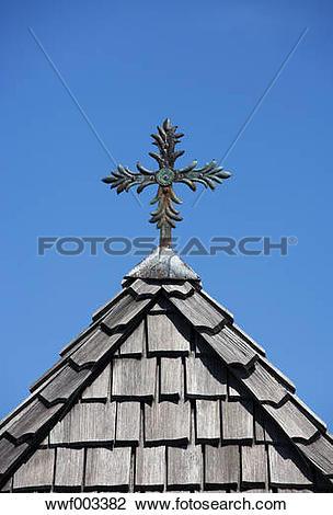 Stock Photo of Austria, Salzkammergut, crucifix on the roof of a.