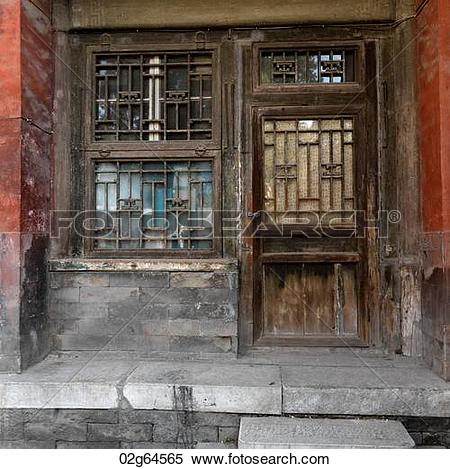 Stock Image of Weathered window with a door of a building at the.