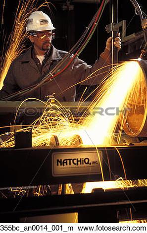Stock Photo of Machine operator running industrial welding machine.