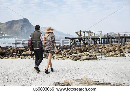 Stock Images of Young couple strolling on beach carrying guitar.