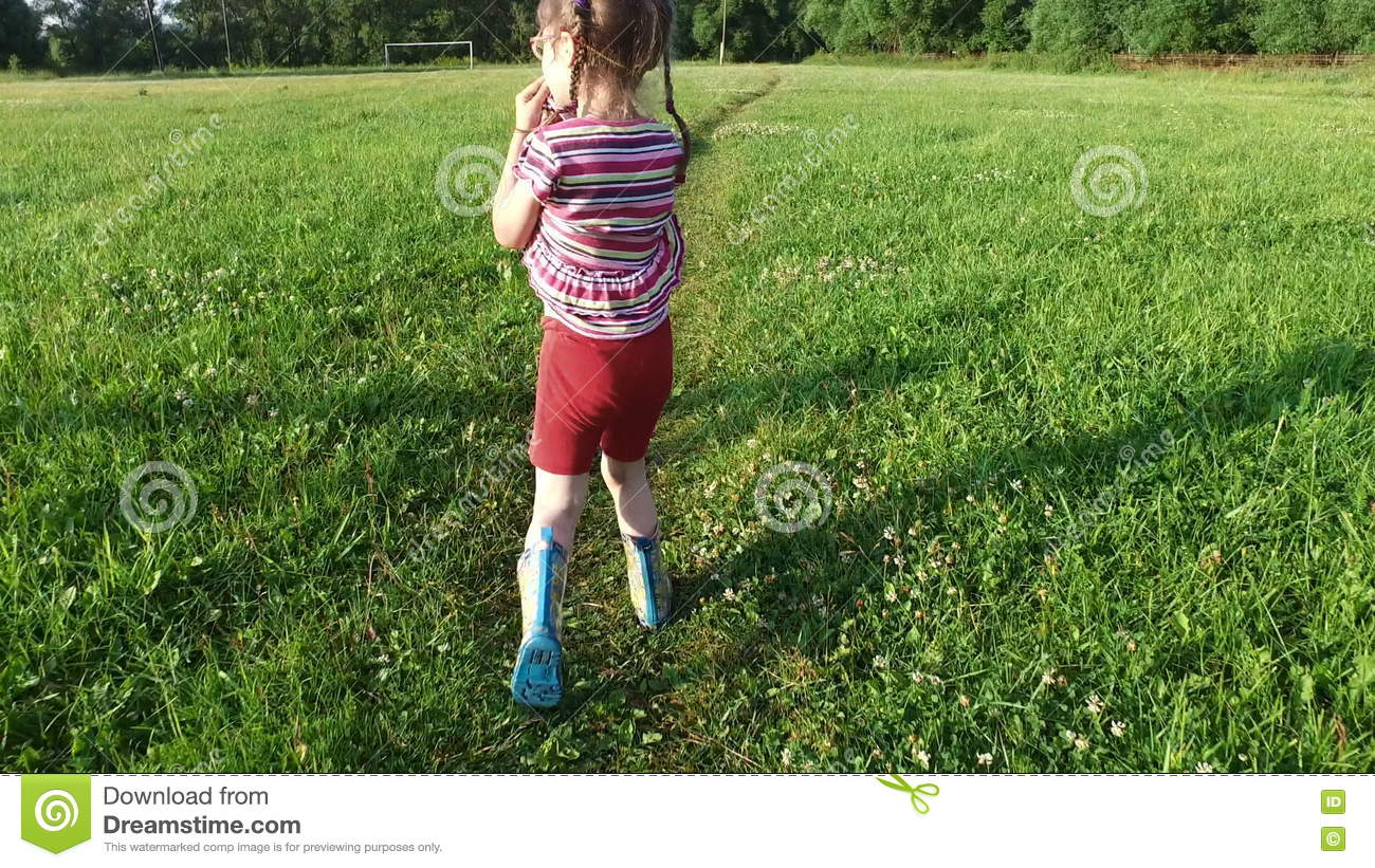 Girl Child Goes To A Large Meadow. Girl Dressed In Boots, Because.
