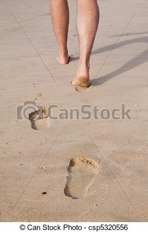 Stock Image of Footprints in wet sand in a line with a man walking.