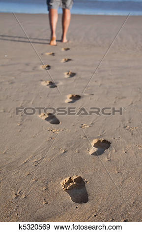 Stock Photograph of Footprints in wet sand in a line with a man.