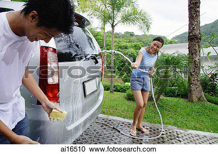 Stock Photography of Couple washing car, woman spraying man with.