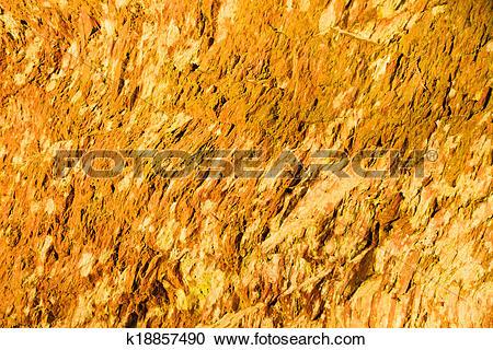Stock Photography of Background of orange wet stone rock wall.