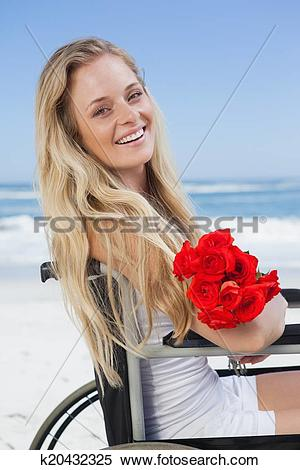 Stock Image of Wheelchair bound blonde smiling at the camera on.