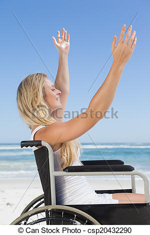 Stock Photographs of Wheelchair bound blonde smiling on the beach.