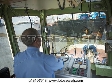 Stock Photo of Captain steering tugboat in wheelhouse u13107643.
