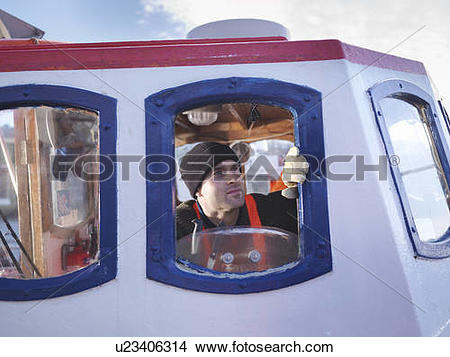 Stock Photo of Fisherman in wheelhouse of fishing boat u23406314.