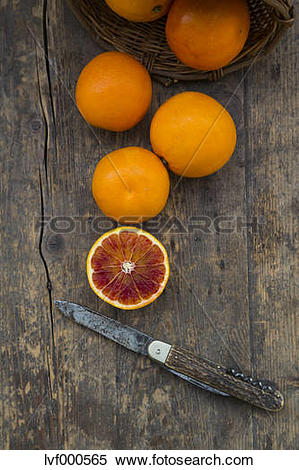Stock Image of Half and whole blood oranges and pocket knife on.