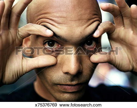 Stock Photograph of Man's face, fingers widening eyes, close.