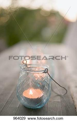 Stock Photograph of Windlight on wooden table in garden 964029.