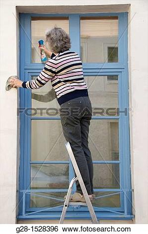 Stock Images of senior woman standing on a step ladder cleaning.