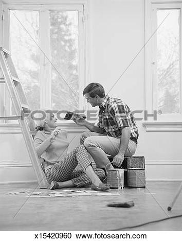 Stock Photography of Young couple besides window and step ladder.