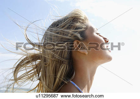 Picture of Young woman on beach with wind.