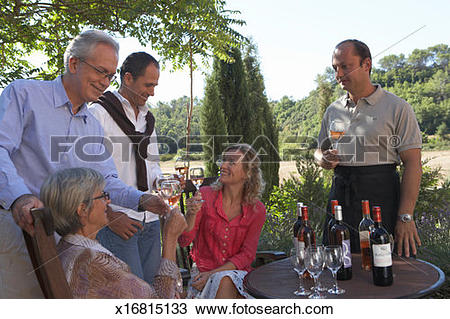 Stock Photo of Two couples with expert at wine tasting on terrace.