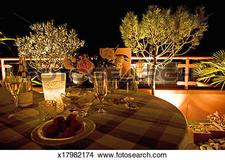 Stock Photo of Wine glasses and flowers on table on terrace, night.