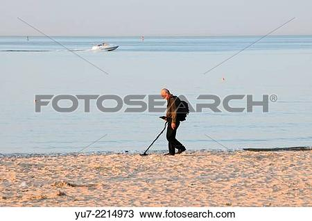 Stock Photo of Man looking for coins buried in sand using metal.