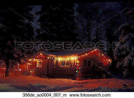 Stock Photo of Log cabin with Christmas lights winter icicles AK.