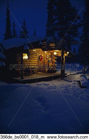 Stock Photo of Interior Alaska Log Cabin Forest Winter Porch Light.