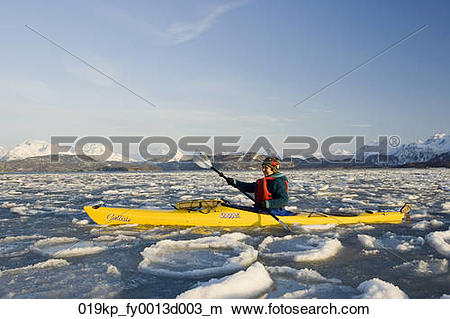 Stock Photo of Women sea kayaking in ice floe of Kachemak Bay near.