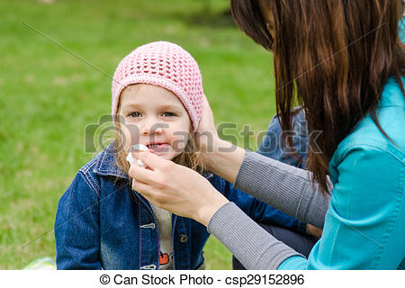 Stock Photographs of Mother wipes his mouth with a napkin girl on.
