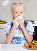 Stock Photography of Little girl wiping mouth with napkin. 2030.