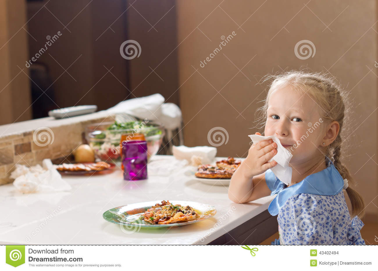 Beautiful Blond Girl Wiping Her Mouth On A Napkin Stock Photo.
