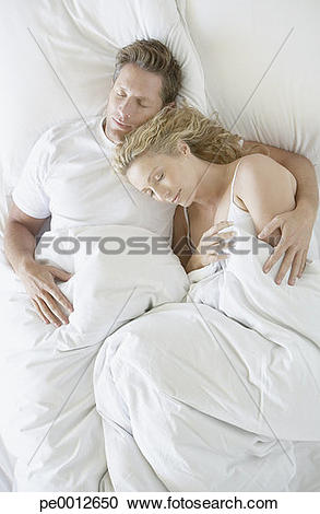 Stock Photography of Man and woman snuggling in bed asleep.