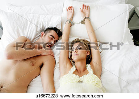 Pictures of Handcuffed woman in bed with man asleep beside.